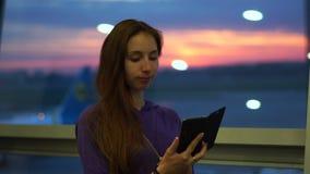Het jonge meisje gebruikt een smartphone, zich bevindt bij de luchthaven wachtend op haar vlucht stock videobeelden