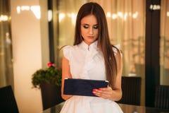 Het jonge meisje gebruikt een tablet en een telefoon aan het werk Het meisje in de koffie glimlacht Royalty-vrije Stock Foto's