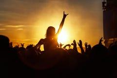 Het jonge meisje geniet van een rotsoverleg, Silhouet op zonsondergang royalty-vrije stock foto
