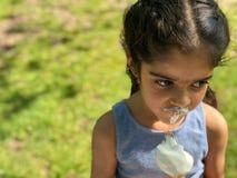 Het jonge meisje geniet van haar roomijs op een zonnige dag stock fotografie