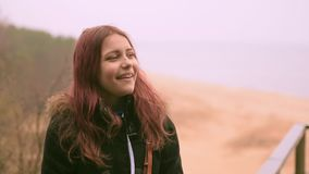 Het jonge meisje geniet van regen in een de lentebos dichtbij overzees Close-up 60 aan 24fps 4K UHD stock video