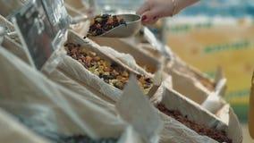 Het jonge meisje giet gedroogd fruit in een pakket stock videobeelden