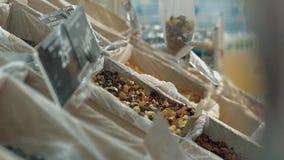 Het jonge meisje giet gedroogd fruit in een pakket stock video