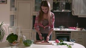 Het jonge meisje hakt tomaat voor de salade stock videobeelden
