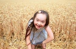 Het jonge meisje heeft pret op tarwegebied Stock Afbeeldingen
