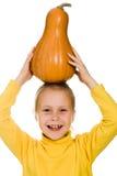 Het jonge meisje hief haar pompoen over zijn hoofd op Royalty-vrije Stock Afbeeldingen