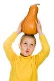 Het jonge meisje hief haar pompoen over zijn hoofd op Stock Afbeelding