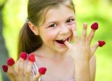 Het jonge meisje houdt frambozen op haar vingers Stock Foto