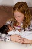 Het jonge meisje houdt haar nicht van de 3 weken oude baby Stock Foto