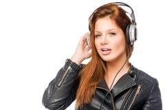 Het jonge meisje houdt van en luistert aan rots met hoofdtelefoons Stock Afbeeldingen