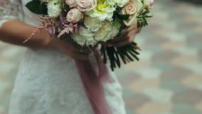 het jonge meisje in huwelijkskleding houdt een boeket van de bruid Mooi huwelijksboeket van bloemen in de handen van stock video
