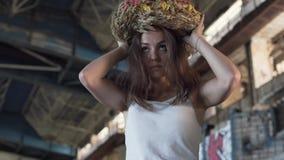 Het jonge meisje kiest tussen een militair GLB en een kroon van tarwe in de verlaten bouw De aantrekkelijke vrouw neemt a stock video