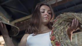 Het jonge meisje kiest tussen een militair GLB en een kroon van tarwe in de verlaten bouw De ongelukkige vrouw neemt een GLB en stock footage
