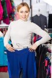 Het jonge meisje kiezen broeken in de opslag Stock Afbeelding