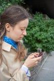 Het jonge meisje kijkt in een smartphone die in zijn handen houdt stock foto's