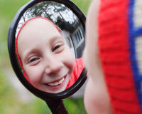 Het jonge meisje kijkt in funhousespiegel Stock Afbeeldingen