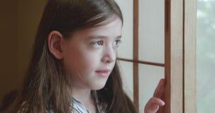 Het jonge meisje kijkt pensively uit een venster met de shojischermen