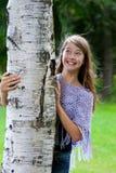 Het jonge meisje kijkt uit van de boom Stock Fotografie