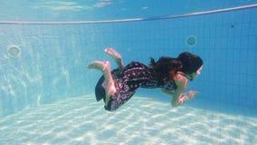 Het jonge meisje in kleding duikt in zwembad stock video