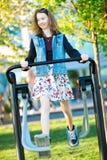 Het jonge meisje kleedde zich in rokoefening die een gymnastiekmachine in werking stelt openlucht stock fotografie