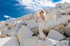 Het jonge meisje kleedde zich in witte, Marmeren steengroeven, enorme witte rotsen, vrouw die lang haar golven Royalty-vrije Stock Foto