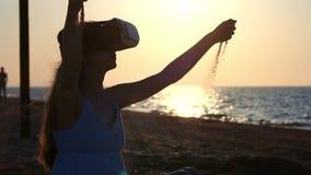 Het jonge meisje kleedt Glazen van virtuele werkelijkheid, VR-Hoofdtelefoon Giet zand door uw vingers uit Zit op het zand door stock footage
