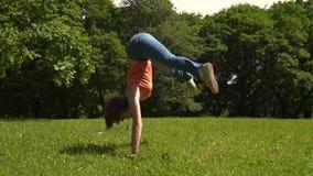 Het jonge meisje krijgt op haar handen die spleten in het groene park doen, dag stock video