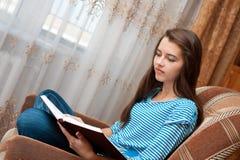 Het jonge meisje leest boek Stock Afbeeldingen