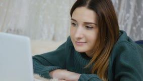 Het jonge meisje legt op vloer met laptop en spreekt met vrienden door webcam stock video