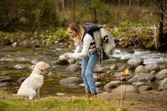 Het jonge meisje leidt en speelt met puppygolden retriever op in de wildernis, naast een rivier royalty-vrije stock fotografie