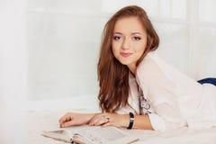 Het jonge meisje ligt en leest het boek Het concept opleiding en Stock Fotografie