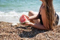 Het jonge meisje ligt op de kust met een watermeloen in haar hand royalty-vrije stock foto's