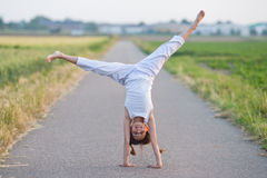 Het jonge meisje maakt een cartwheel op een weg stock fotografie