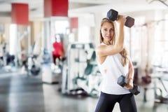 Het jonge meisje maakt oefeningen met gewicht in gymnastiek Stock Fotografie