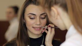 Het jonge meisje maakt vrouw in schoonheidssalon op stock footage