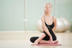 Het jonge meisje mediteert in sporten aan een gymnastiek Royalty-vrije Stock Foto's