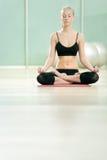 Het jonge meisje mediteert in sporten aan een gymnastiek Stock Foto's