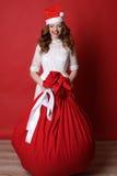 Het jonge meisje met charmante glimlach, in Kerstmanhoed, met grote zak met stelt voor Royalty-vrije Stock Foto's