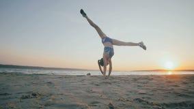 Het jonge meisje met een slank cijfer is op zee bezig geweest met gymnastiek bij zonsopgang Onherkenbaar silhouet stock footage