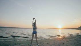 Het jonge meisje met een slank cijfer is op zee bezig geweest met gymnastiek bij zonsopgang Onherkenbaar silhouet stock videobeelden