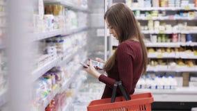 Het jonge meisje met een telefoon en een kruidenierswinkelmand in haar hand kiest producten in opslag stock footage