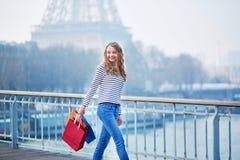 Het jonge meisje met het winkelen doet dichtbij de toren van Eiffel in zakken stock afbeelding