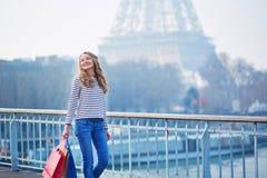 Het jonge meisje met het winkelen doet dichtbij de toren van Eiffel in zakken royalty-vrije stock fotografie