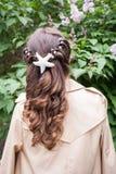 Het jonge meisje met krullend haar bevindt zich dichtbij bloeiende lilac struik en bekijkt het Achter mening Stock Foto