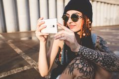 Het jonge meisje met tatoegeringen en dreadlocks in een blauw GLB gebruikt een smartphone tegen de achtergrond van een concrete m royalty-vrije stock afbeelding