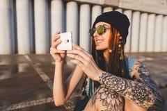Het jonge meisje met tatoegeringen en dreadlocks in een blauw GLB gebruikt een smartphone tegen de achtergrond van een concrete m stock foto