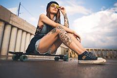 Het jonge meisje met tatoegeringen en dreadlocks in een blauw GLB zit op een longboard tegen de achtergrond van betonconstructie royalty-vrije stock foto's