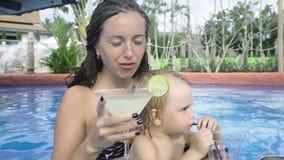 Het jonge meisje met weinig kindzitting in zwembadbar en drinkt cocktail stock footage