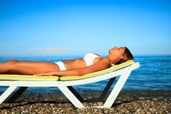 Het jonge meisje neemt een zonbad stock foto