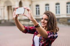 Het jonge meisje neemt selfie uit handen met telefoon op concept van het de straat het stedelijke leven van de de zomerstad royalty-vrije stock fotografie